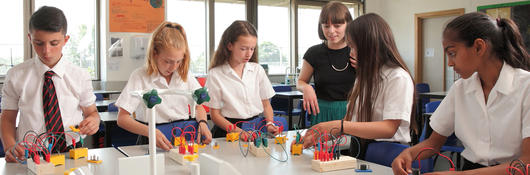A group of children conducting a physics experiment with their teacher.