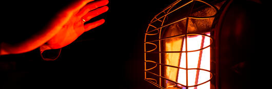 Image of warming hands by gas heater relating to the thermal store of energy