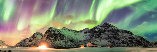 The northern lights above snow-capped mountains.